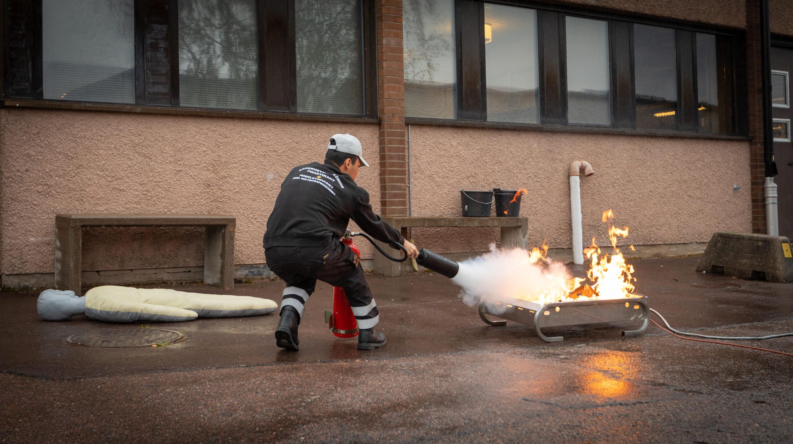 En elev med yrkesutgång väktare använder en brandsläckare för att släcka eld i ett oljefat som en del i kursen systematiskt brandskyddsarbete.