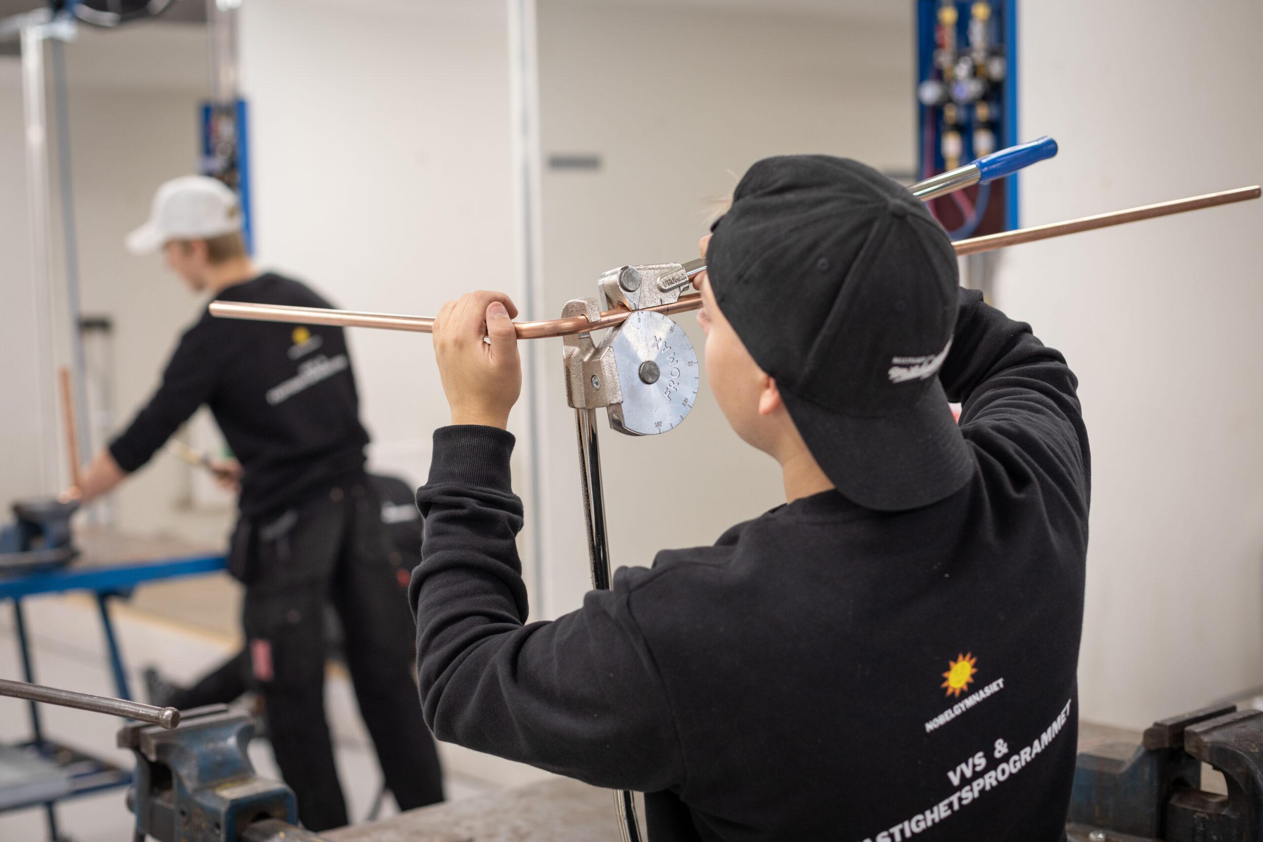 En elev bockar kopparrör som ska användas vid installationen av en WC-stol.