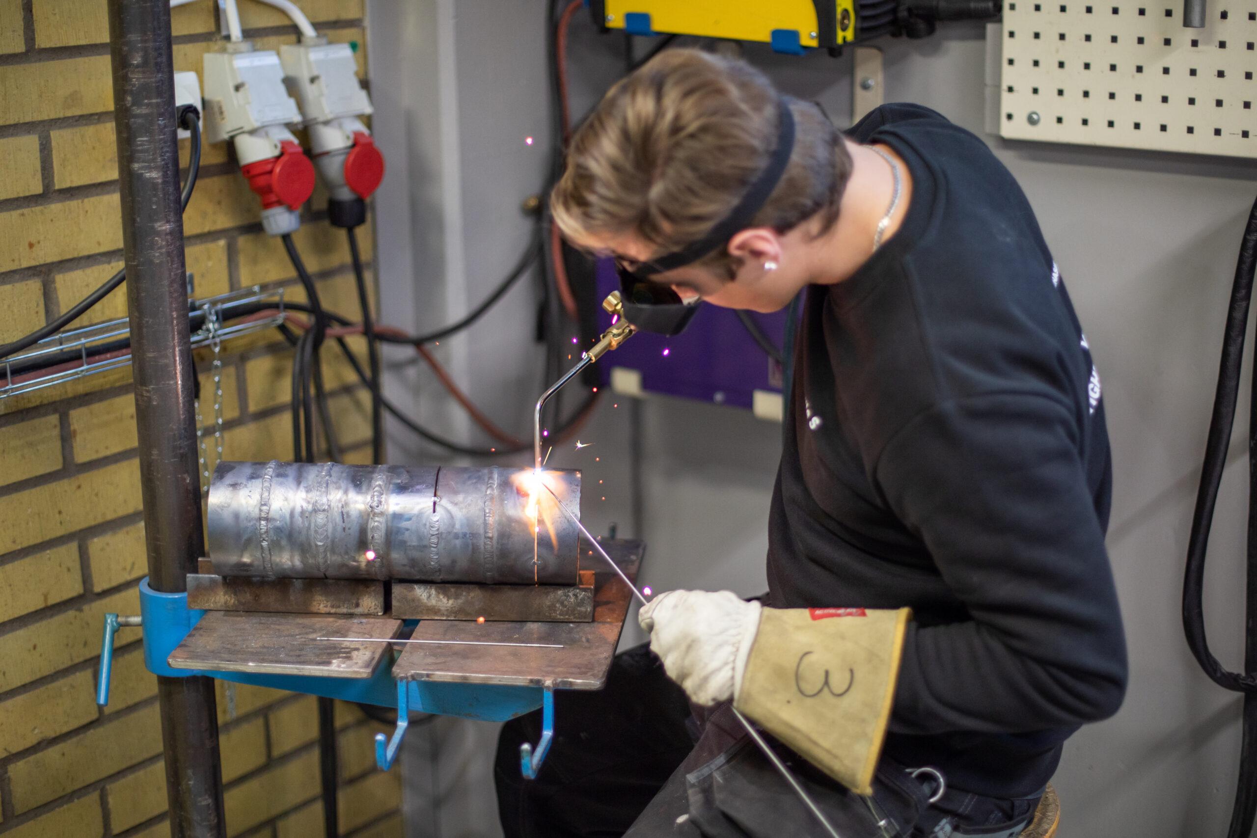 En elev, med svetsglasögon och -handskar, övar på att gassvetsa rör.