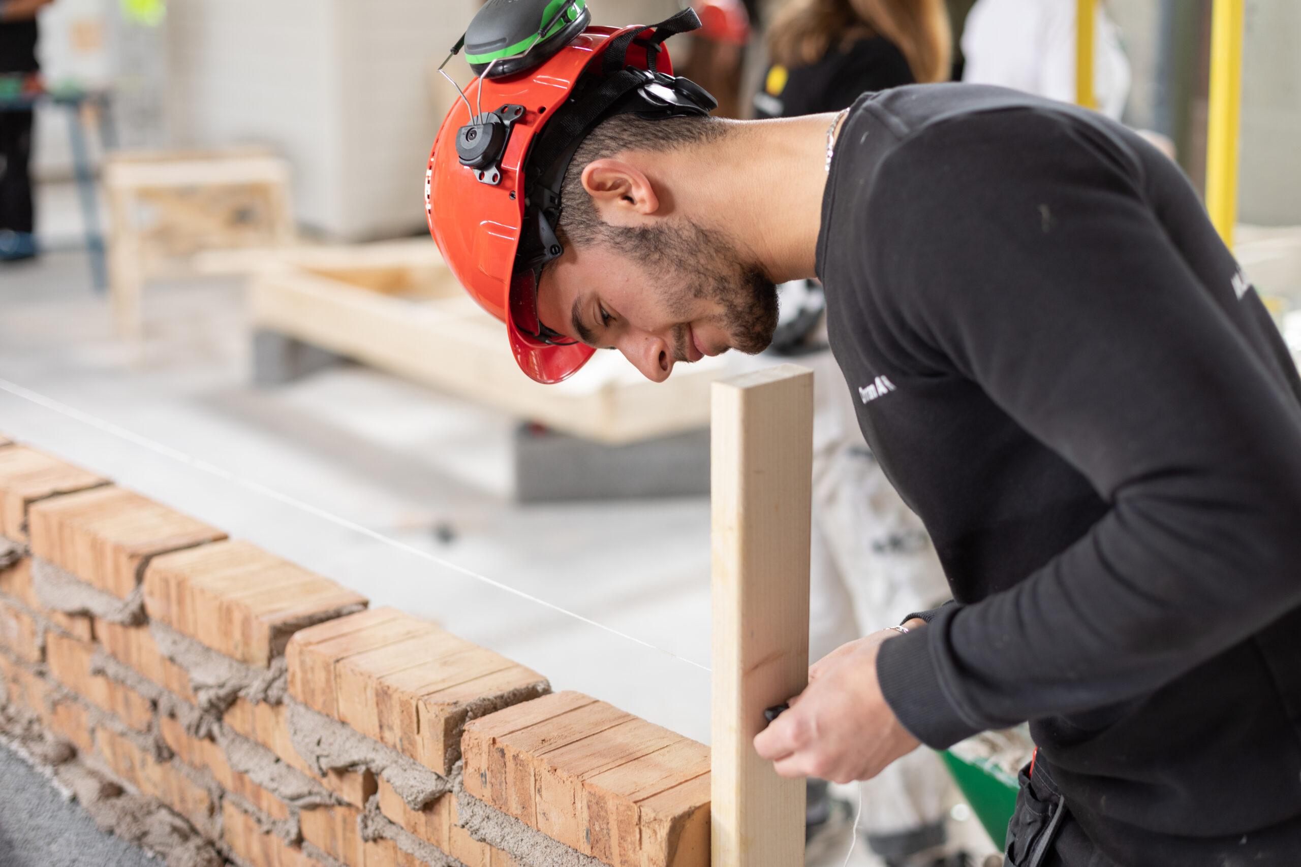 En elev justerar murarsnöret så att tegelstenen hamnar i rätt höjd och riktning då han lägger sin sten i den blivande muren.