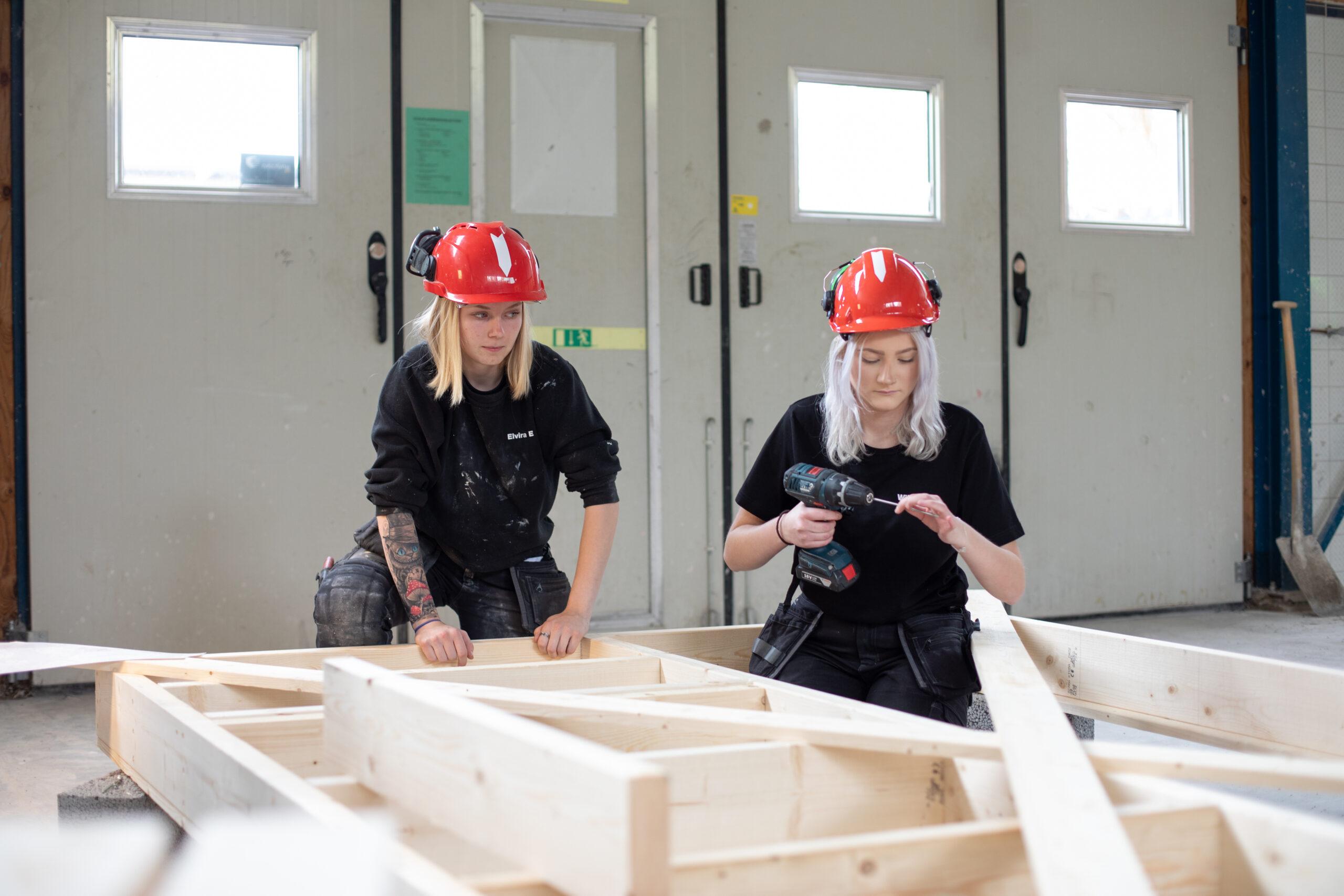 Två elever bygger grunden till en lekstuga i trä.