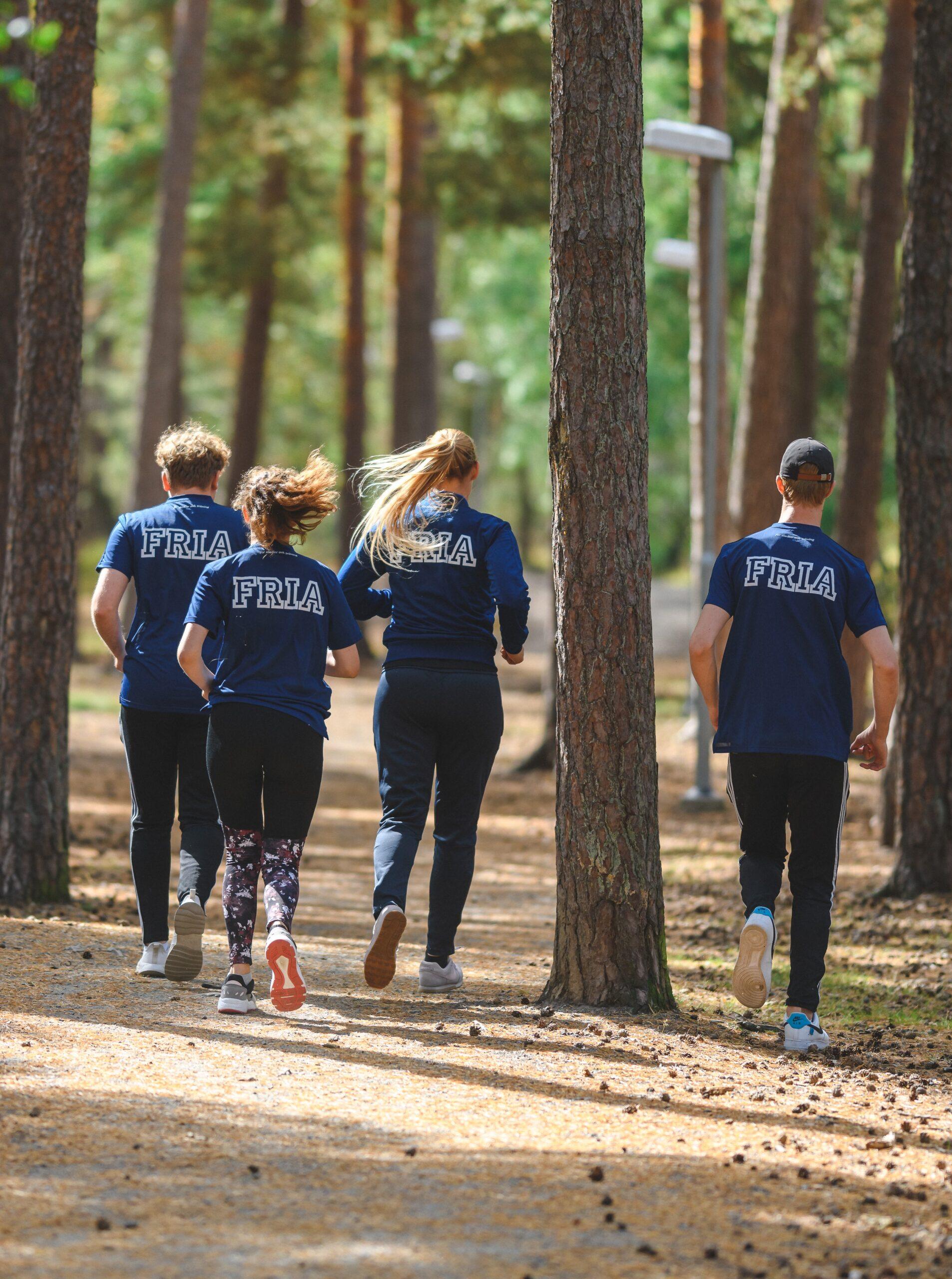 Elever joggar i skogen