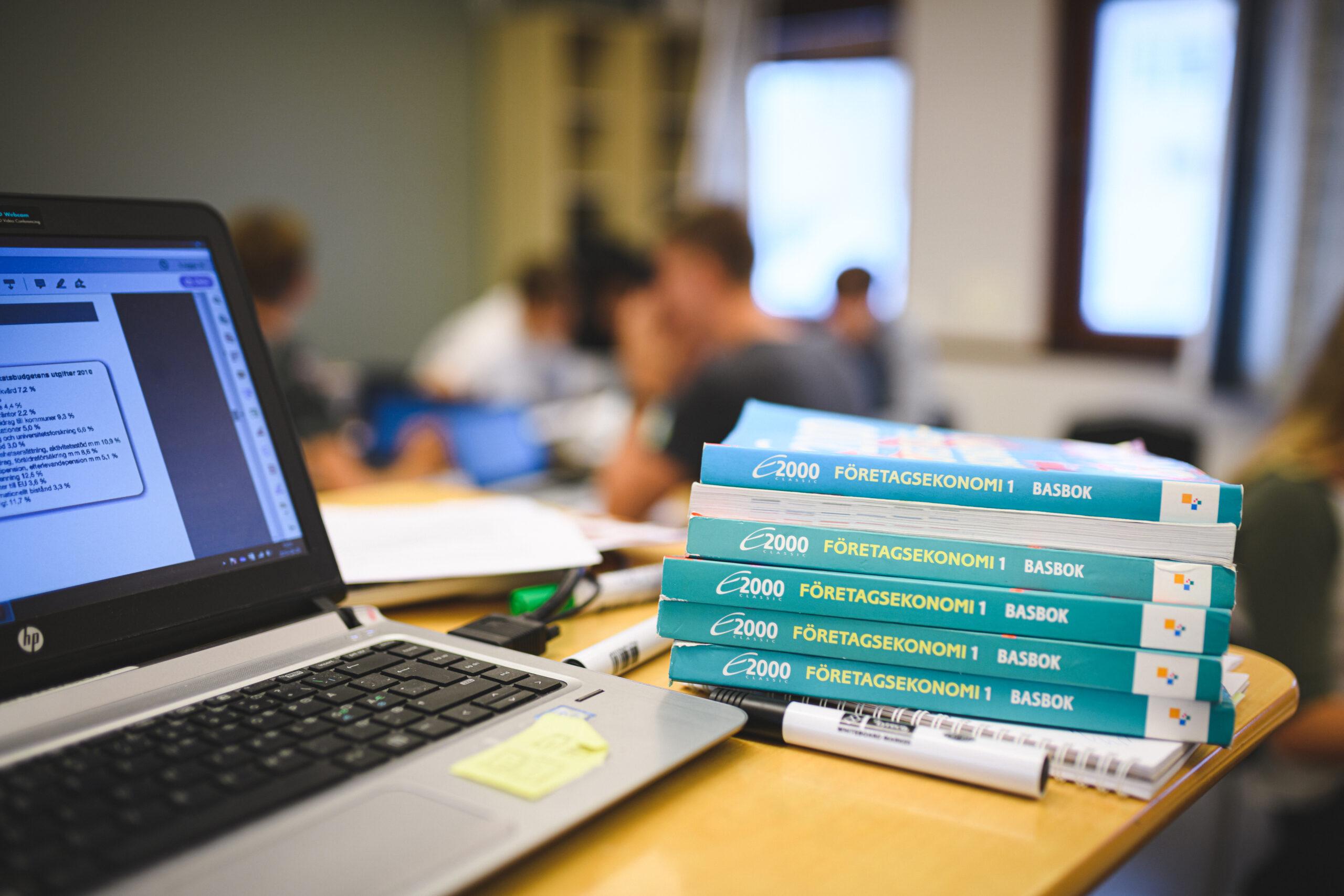 En laptop och böcker inom Företagsekonomi 1 ligger på ett ståbord.