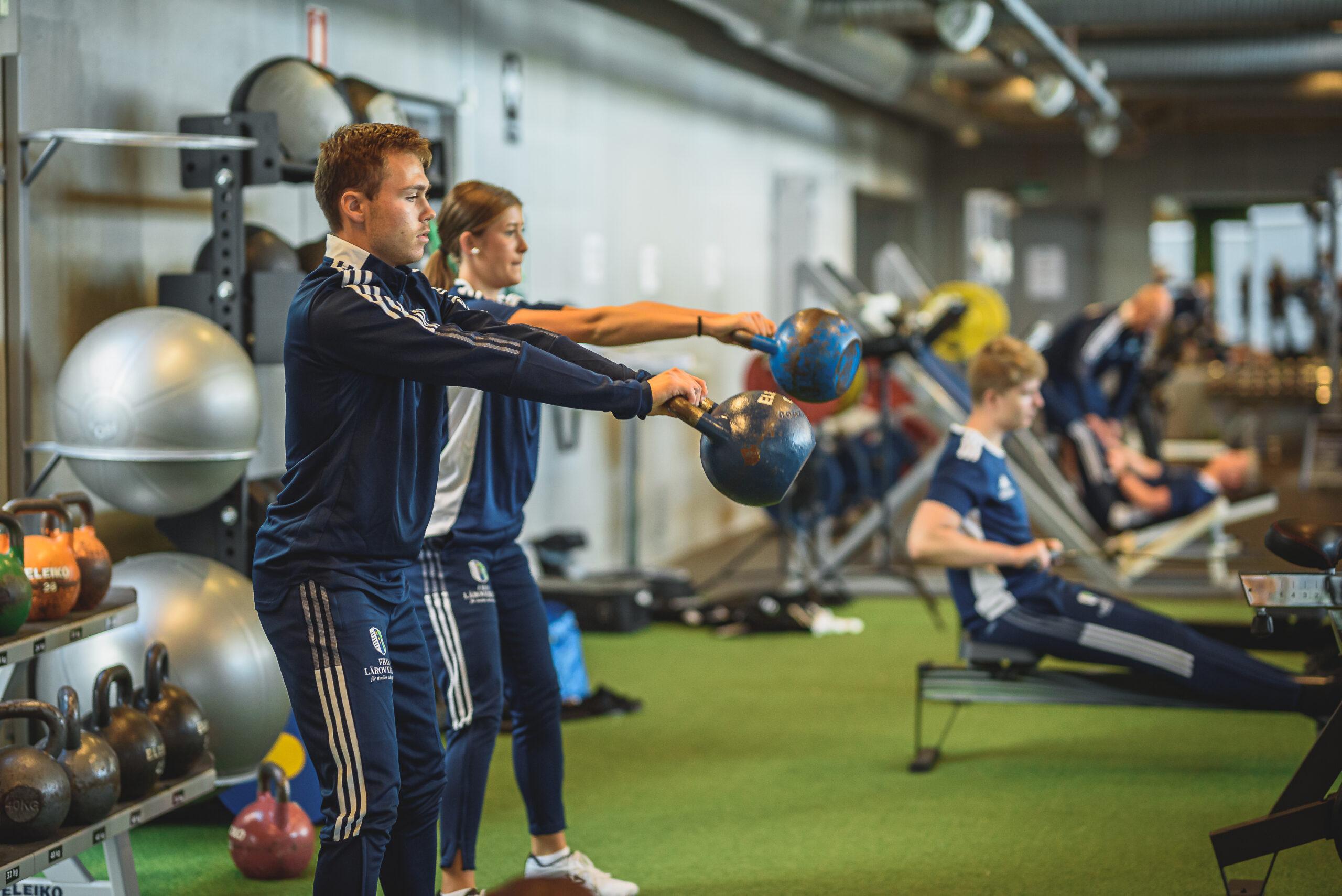 Två elever tränar med kettlebell på gymmet.