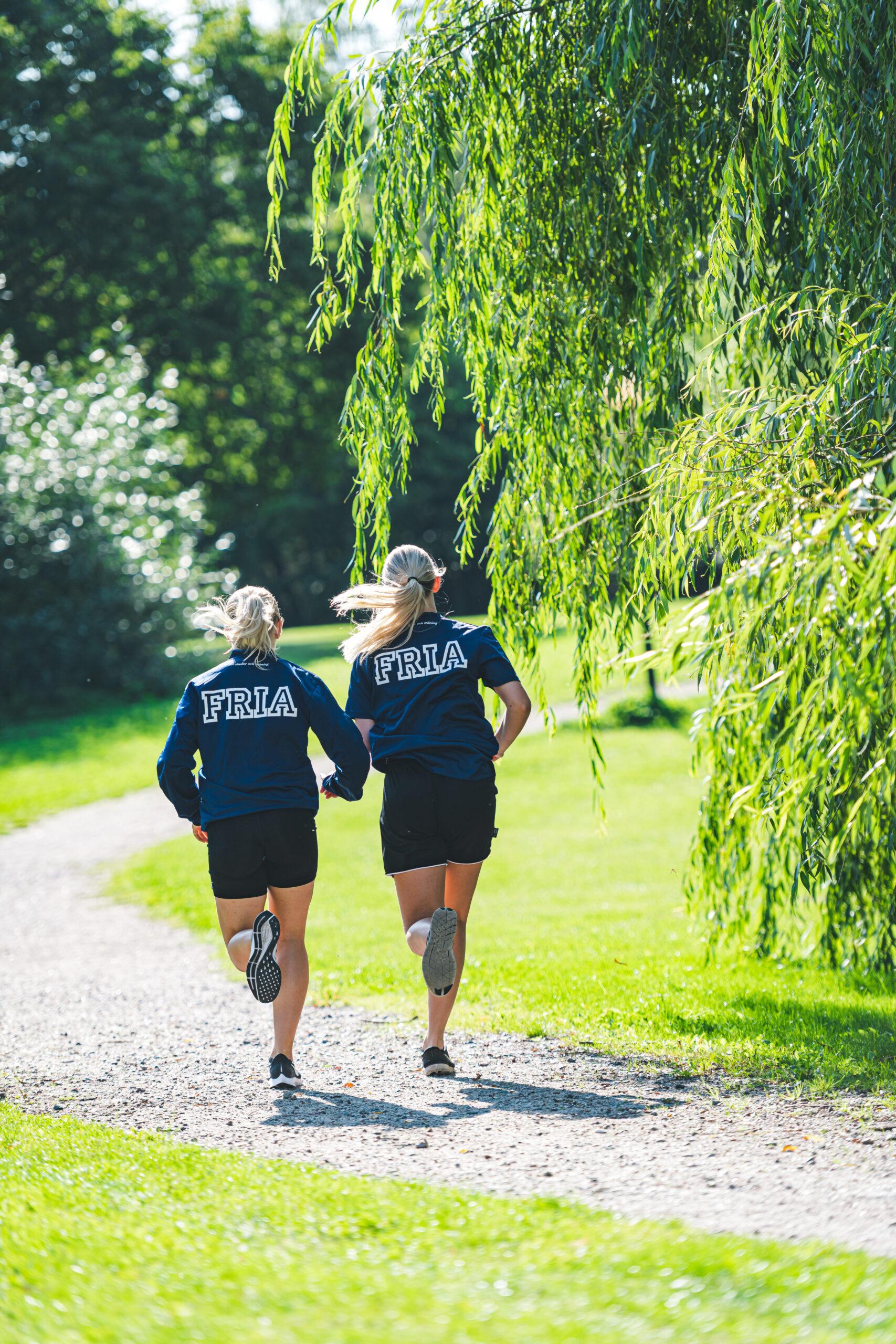 Två tjejer i träningskläder med Fria-logga joggar ute i naturen