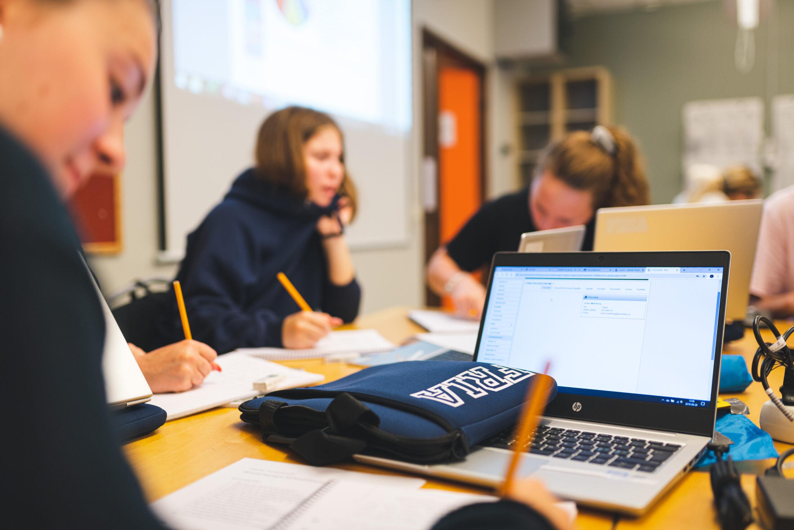 Fem elever sitter runt ett bord i ett klassrum och löser en skoluppgift.