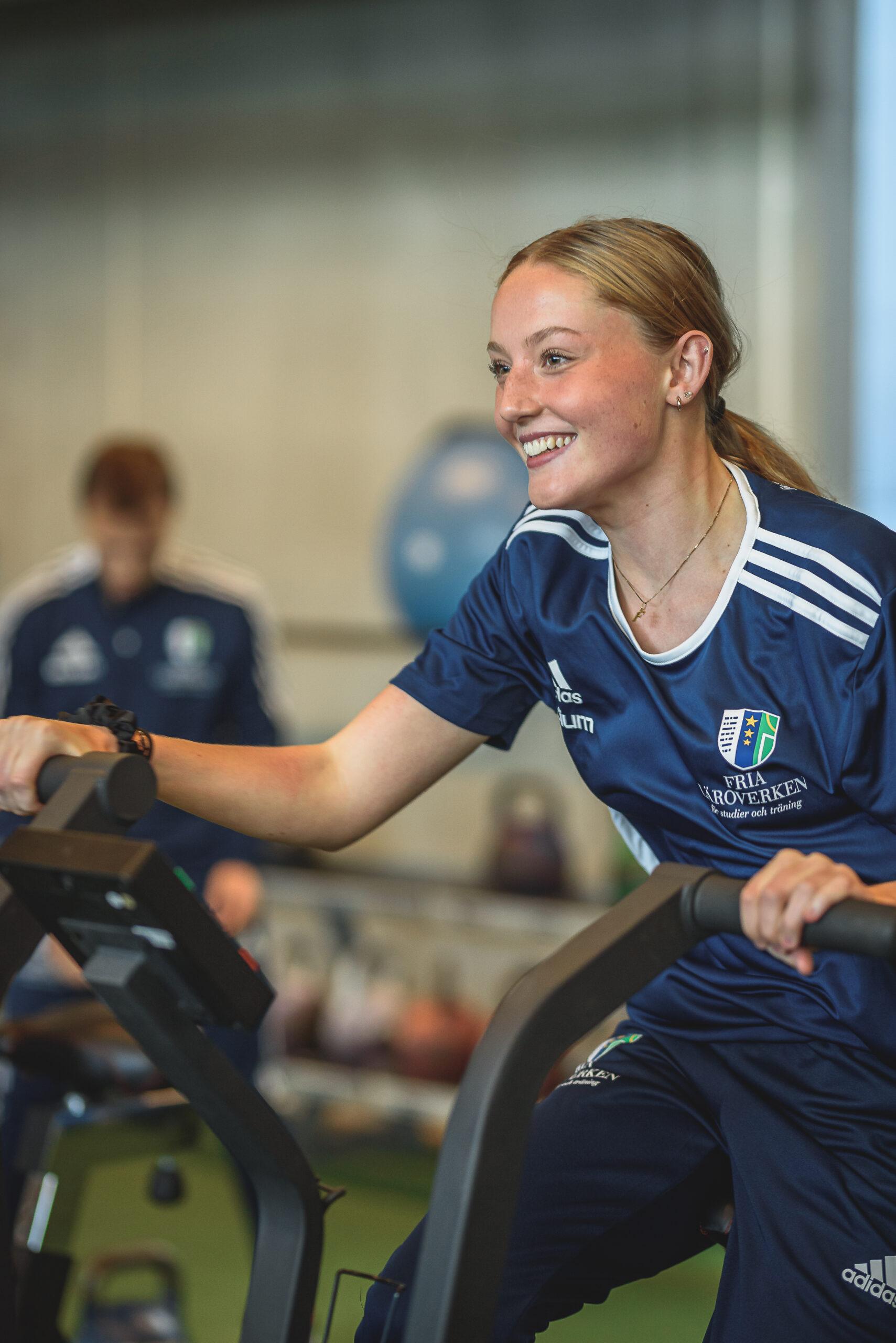 En tjej cyklar på en motionscykel på gymmet
