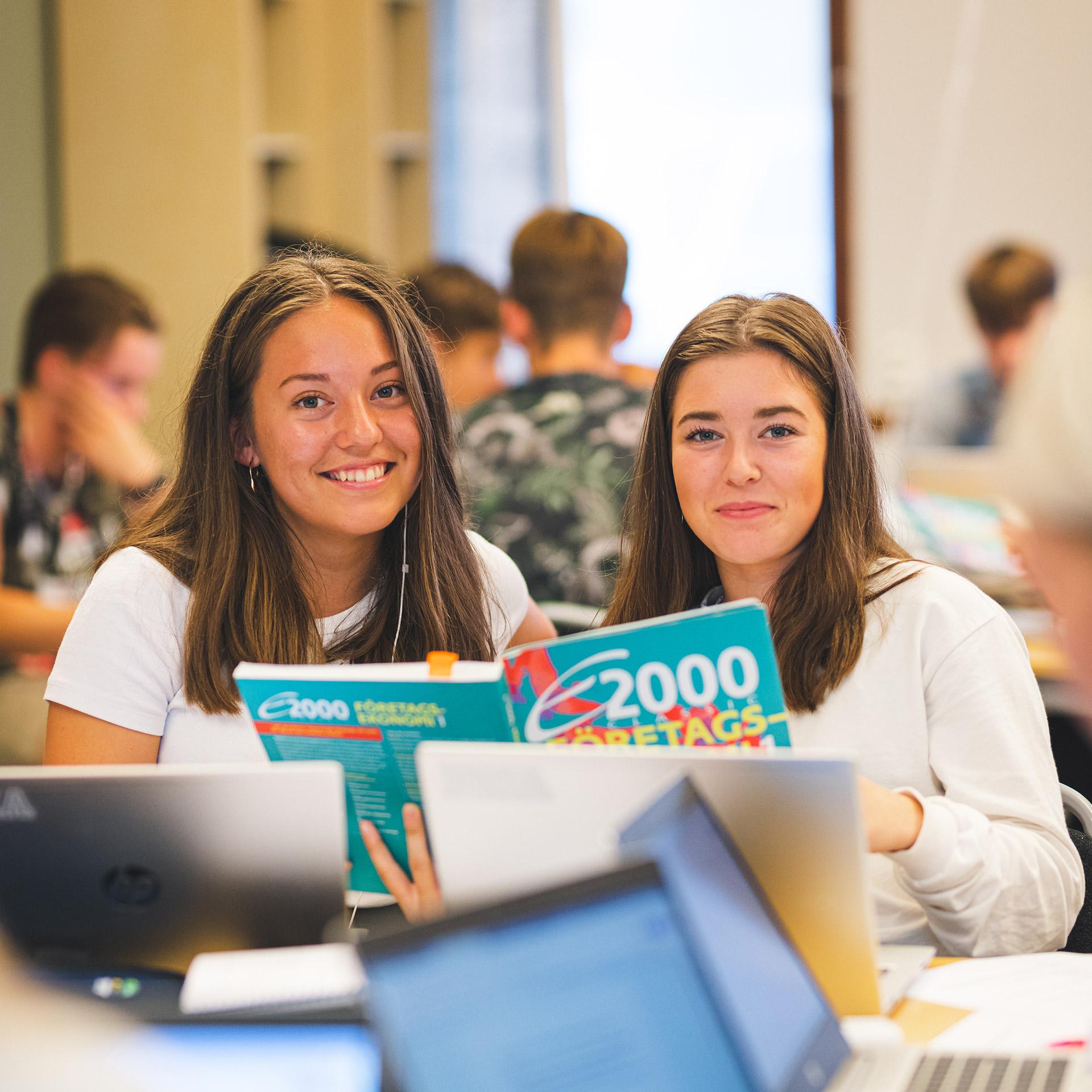 Karlstad Fria läroverk – Ekonomiprogrammet. Två elever håller upp en bok inom Företagsekonomi 1.