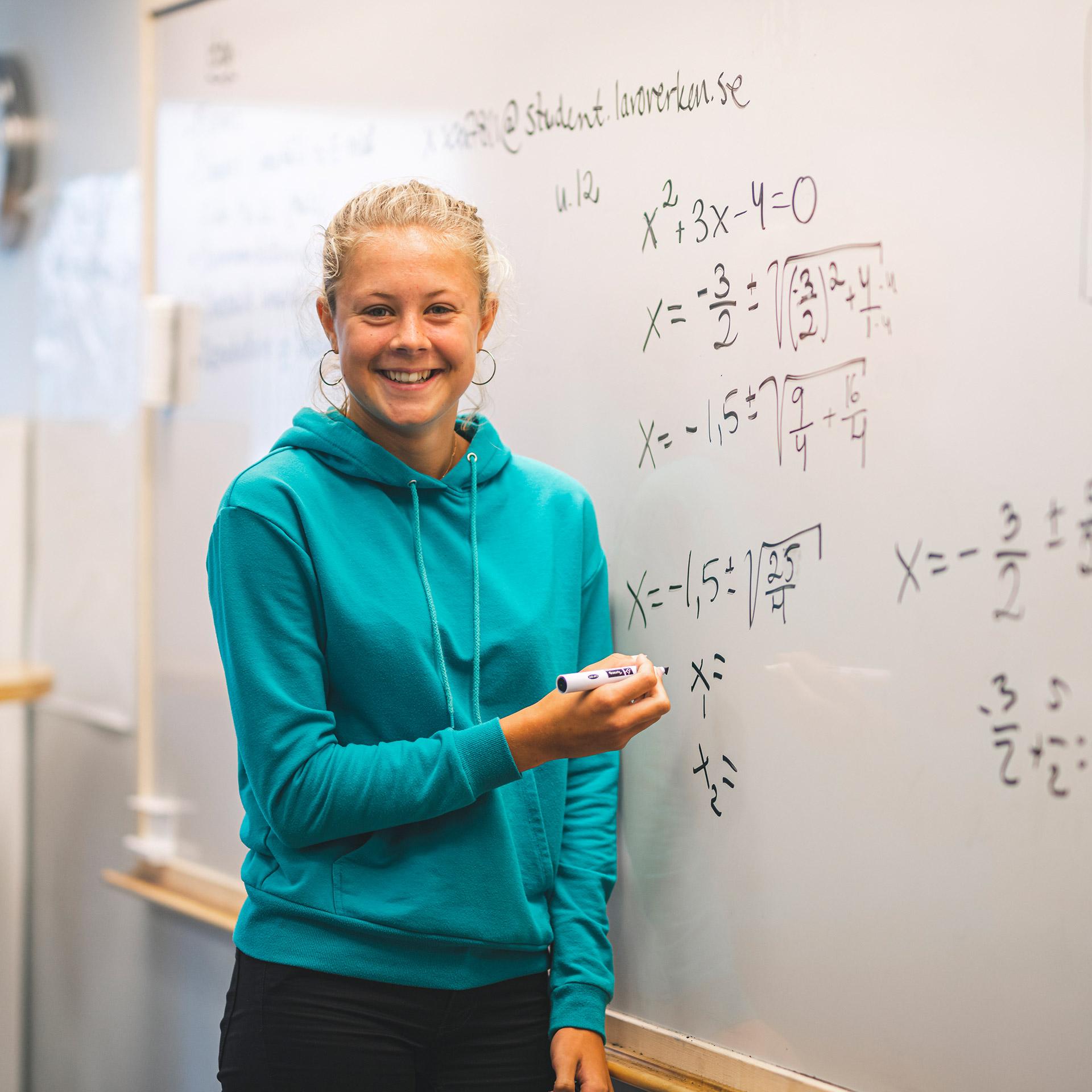 En elev skriver ekvationstal på whiteboardtavlan