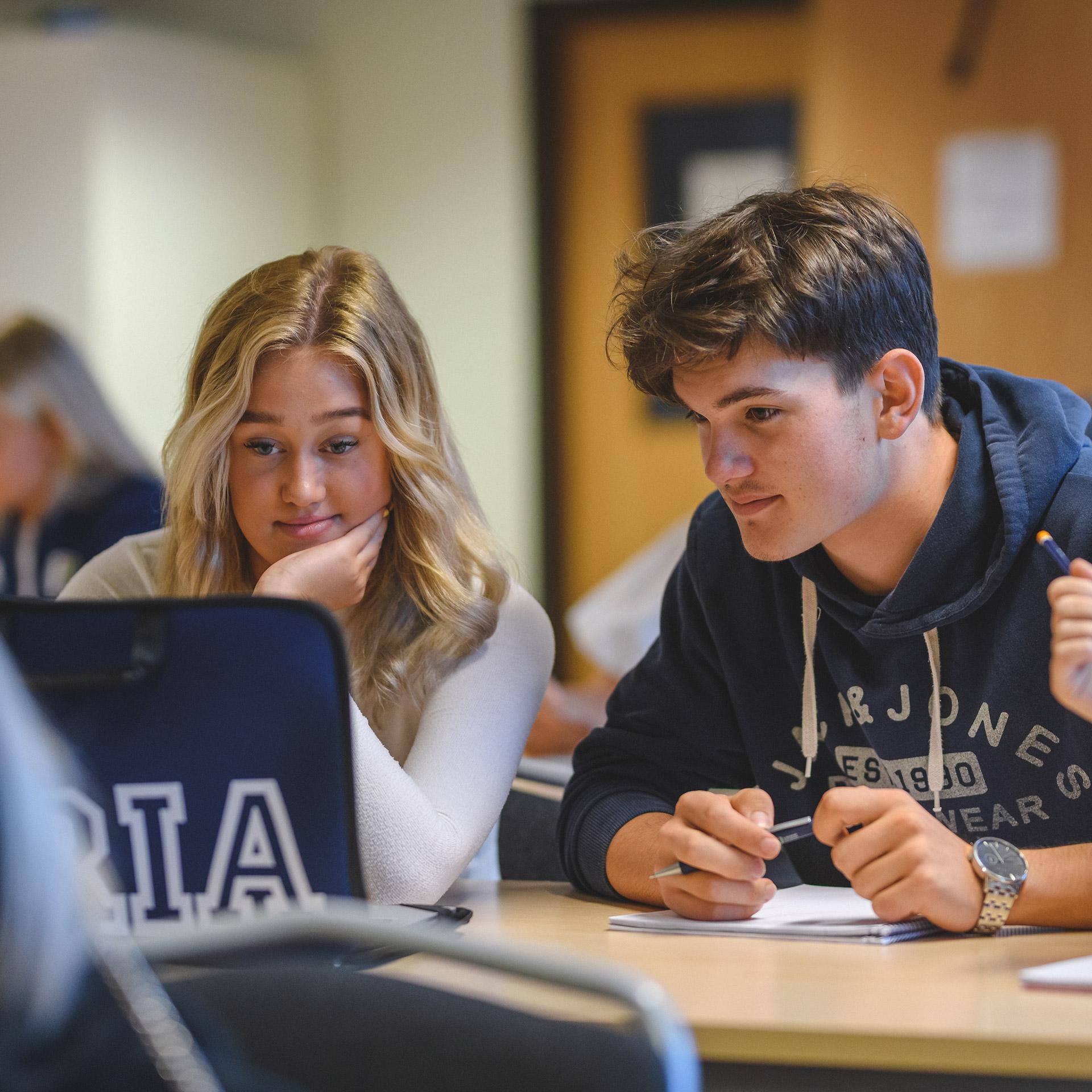 Tre elever tittar på en laptop och löser skoluppgifter tillsammans.