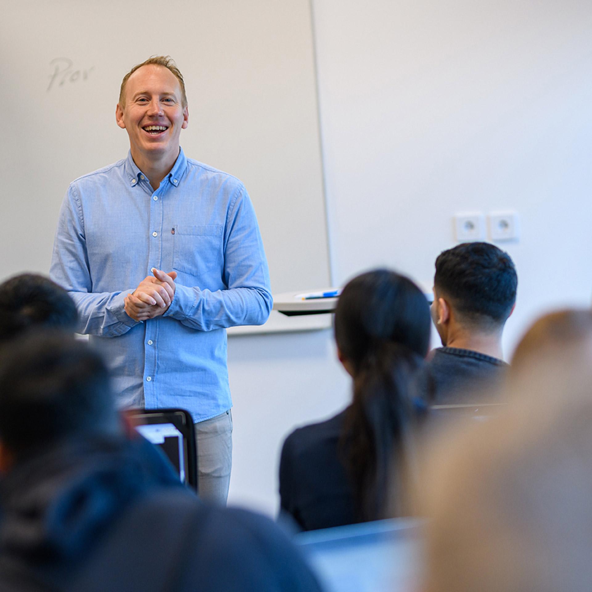 En manlig lärare står framför whiteboardtavlan och undervisar elever