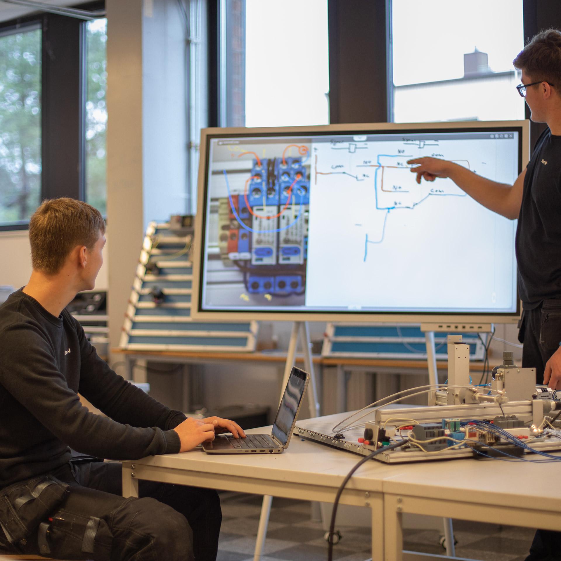 Två elever går igenom ritningslära och programmering av styr- och reglerteknik.