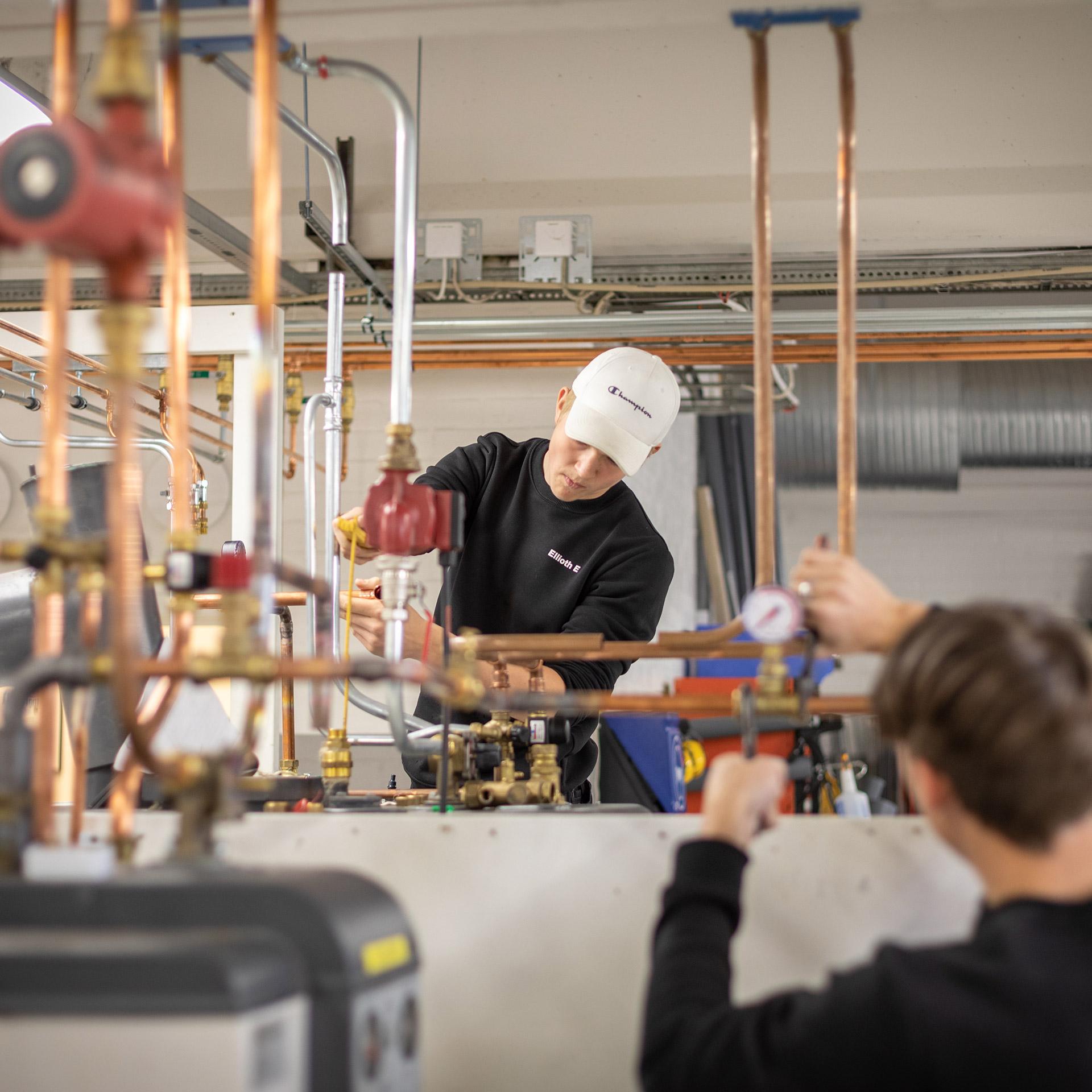Två elever installerar en värmepanna.